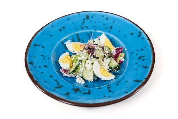Sabrosa ensalada con verduras y huevos en plato hermoso