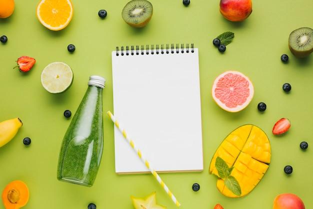 Sabrosa fruta fresca y jugo con cuaderno copyspace