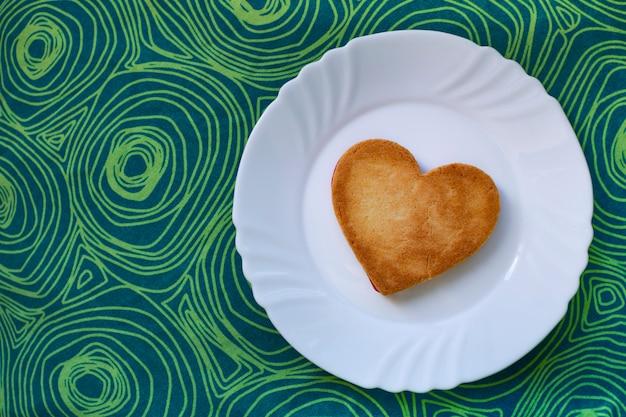 Sabrosa galleta en forma de corazón, para el día de san valentín, preparada en un plato blanco