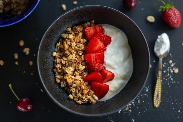 Sabrosa granola casera con sabor a fruta muesli servida en un tazón con yogur sobre fondo oscuro. de cerca