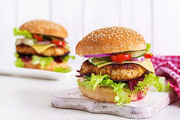 Sabrosa hamburguesa casera a la parrilla con hamburguesa de pollo, tomate, queso, pepino, lechuga y remolacha. emparedado. almuerzo