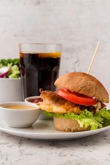 Sabrosa hamburguesa casera con salsa y refresco