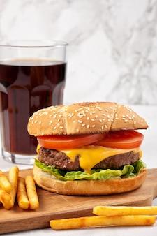 Sabrosa hamburguesa fresca con queso, tomate y ensalada con papas fritas y cola