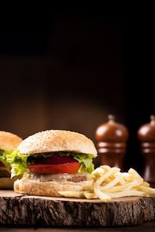 Sabrosa hamburguesa de ternera a la parrilla con lechuga, queso y cebolla servida en una tabla de cortar con copyspace