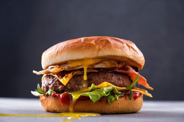 Sabrosa hamburguesa de ternera a la parrilla tocino frito y huevos, queso, tomate y lechuga.
