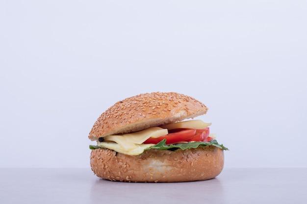 Sabrosa hamburguesa con tomate, queso, lechuga sobre superficie blanca.