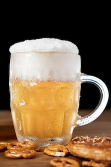 Sabrosa jarra de cerveza con espuma y pretzels