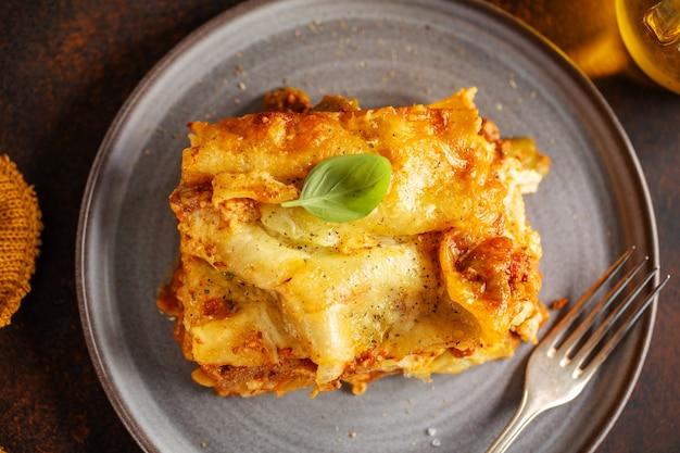 Sabrosa lasaña italiana clásica preparada al horno en cazuela sobre fondo brillante. de cerca