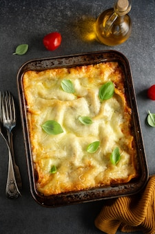 Sabrosa lasaña italiana clásica preparada al horno en cazuela sobre fondo brillante. vista superior.