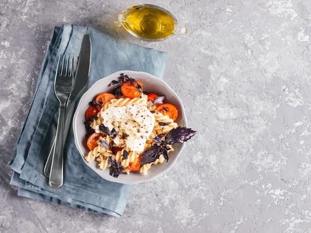Sabrosa pasta italiana fusilli con cereza, queso mozarella o buratta y albahaca fresca. plato con pasta sobre fondo de hormigón gris. vista superior.