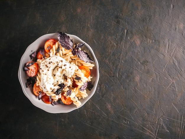 Sabrosa pasta italiana fusilli con cereza, queso mozarella o buratta y albahaca fresca. plato con pasta sobre fondo negro de hormigón. vista superior.