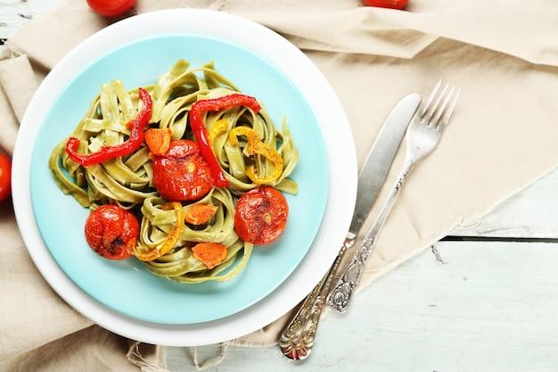 Sabrosa pasta con pimiento, zanahoria y tomate en mesa de madera