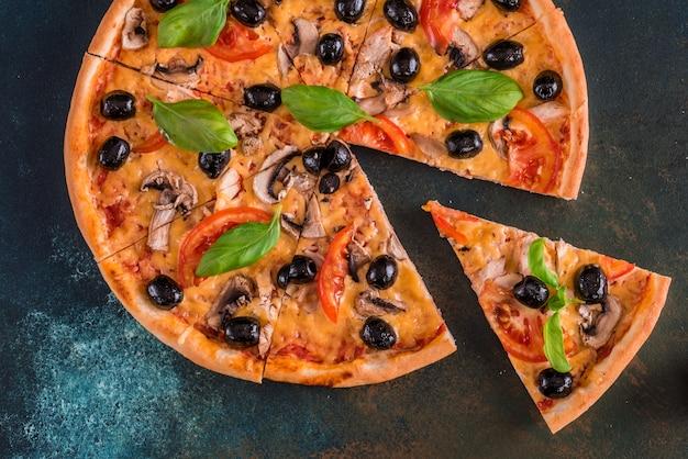 Sabrosa pizza caliente fresca contra un fondo oscuro