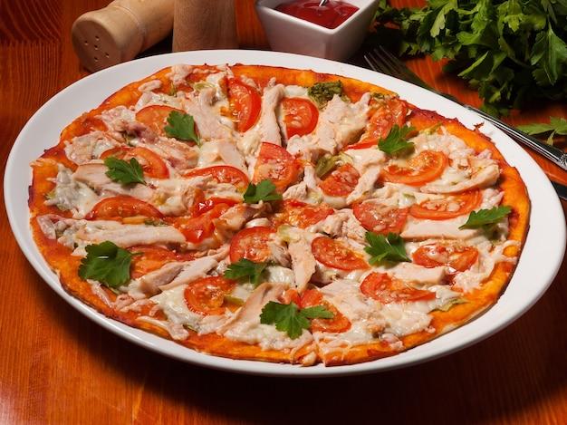 Sabrosa pizza césar en un plato blanco sobre una mesa de madera con salsa de tomate