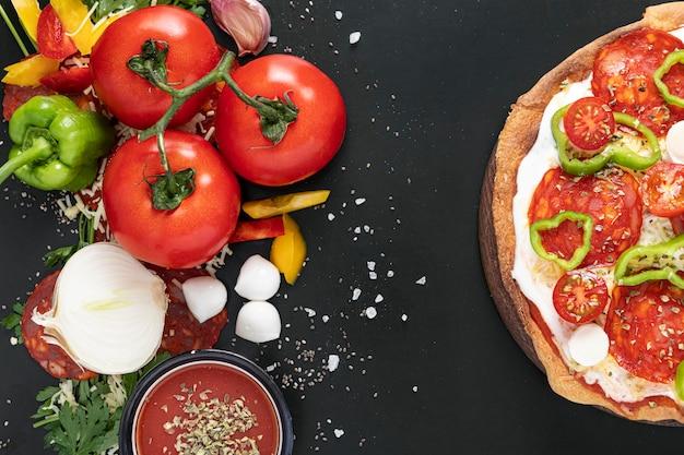 Sabrosa pizza e ingredientes al lado