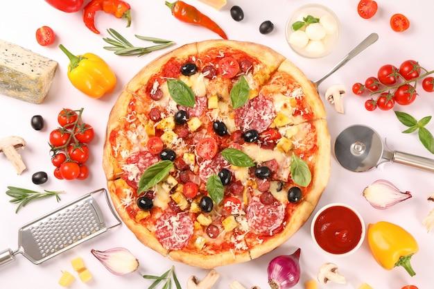 Sabrosa pizza, ingredientes y suministros de cocina sobre fondo blanco.