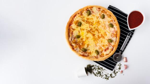 Sabrosa pizza italiana y salsa de tomate con cortador de pizza en mantel sobre fondo blanco.