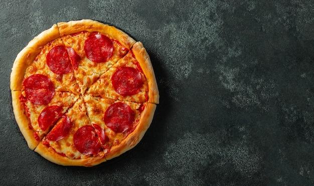 Sabrosa pizza de pepperoni e ingredientes para cocinar.