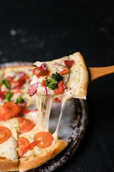 Sabrosa pizza en rodajas con hojas de albahaca en mesa negro