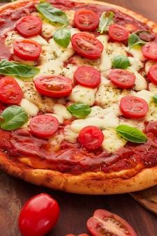 Sabrosa pizza con rodajas de tomate; albahaca y queso