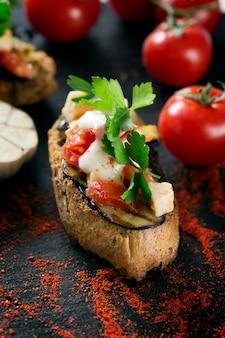 Sabrosa sabrosa tomate italiano bruschetta, en rodajas de baguette tostado adornado con perejil y berenjena