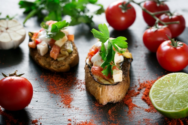 Sabrosa sabrosa tomate italiano bruschetta, en rodajas de baguette tostado adornado con perejil