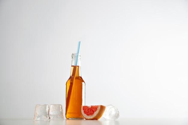 Sabrosa sidra fresca en botella transparente con pajita azul cerca de cubitos de hielo y rodaja de pomelo rojo aislado en blanco