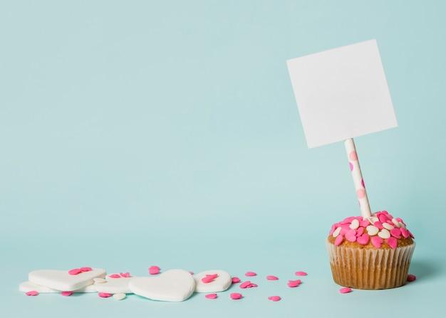 Sabrosa tarta con etiqueta en palo y corazones decorativos.