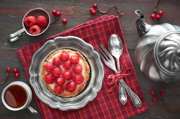 Sabrosa tarta de frambuesa en una placa de metal vintaege con tetera y una taza de té en una servilleta roja a cuadros