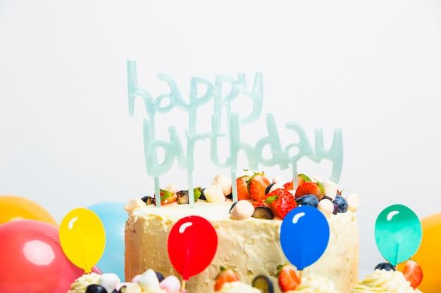Sabrosa tarta fresca con frutos rojos y título de feliz cumpleaños cerca de un juego de globos