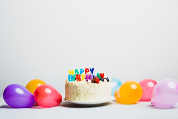 Sabrosa tarta con frutos rojos y título de feliz cumpleaños cerca de globos