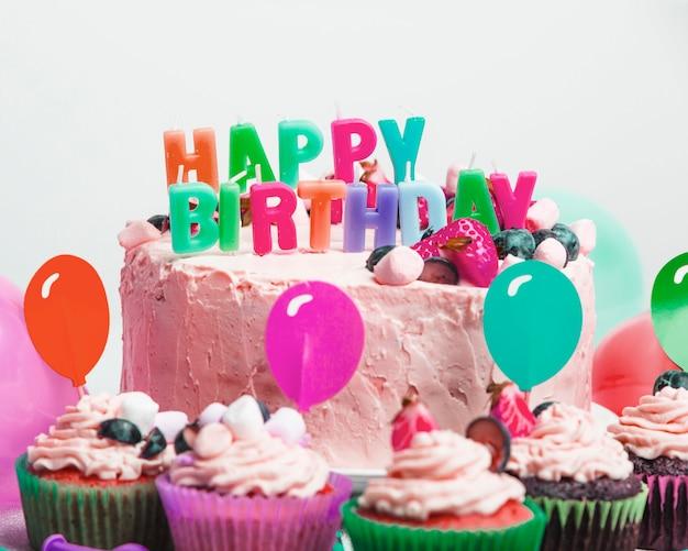 Sabrosa tarta con frutos rojos y título de feliz cumpleaños cerca de un juego de magdalenas