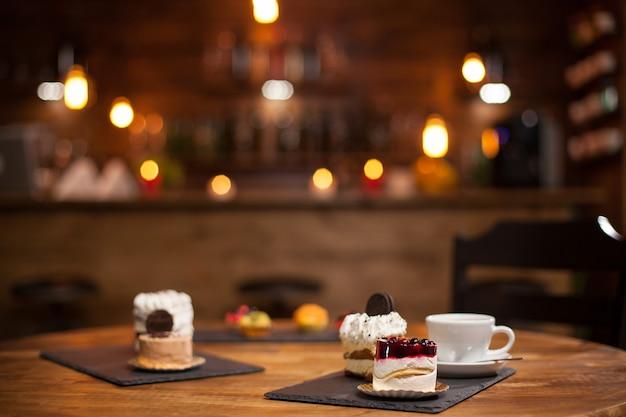 Sabrosa taza de café nuevos deliciosos mini pasteles con diferentes formas sobre una mesa de madera en una cafetería.