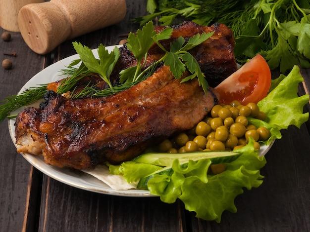 Sabrosas costillas de cerdo sobre brasas en un plato servido con verduras