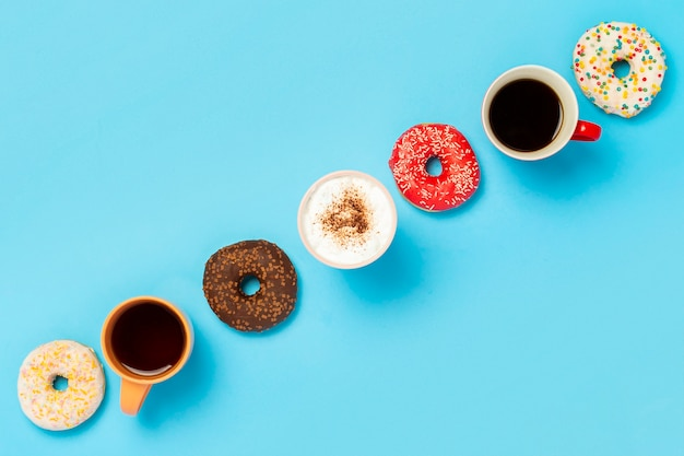 Sabrosas donas y tazas con bebidas calientes, café, capuchino, vista superior de té