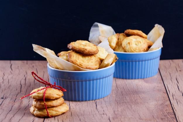 Sabrosas galletas caseras en platos azules con papel pergamino, sobre la mesa
