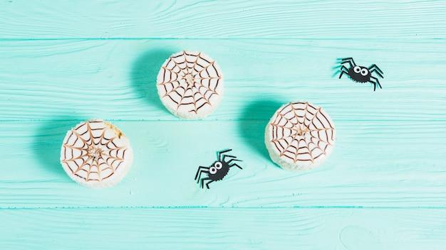 Sabrosas galletas cerca de arañas decoradoras