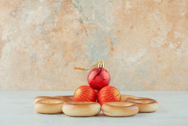 Sabrosas galletas dulces redondas con bolas de navidad rojas sobre fondo blanco. foto de alta calidad
