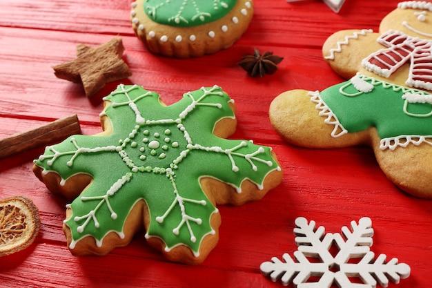 Sabrosas galletas de navidad y decoración en mesa de madera roja, vista cercana