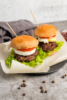 Sabrosas hamburguesas en mesa gris