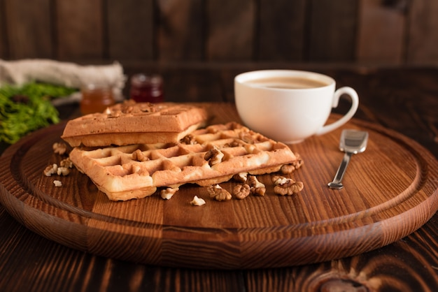 Sabrosas obleas frescas de viena, mermelada y taza de café sobre un fondo de madera oscuro