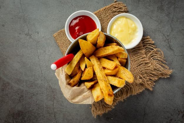 Sabrosas papas fritas sobre fondo oscuro