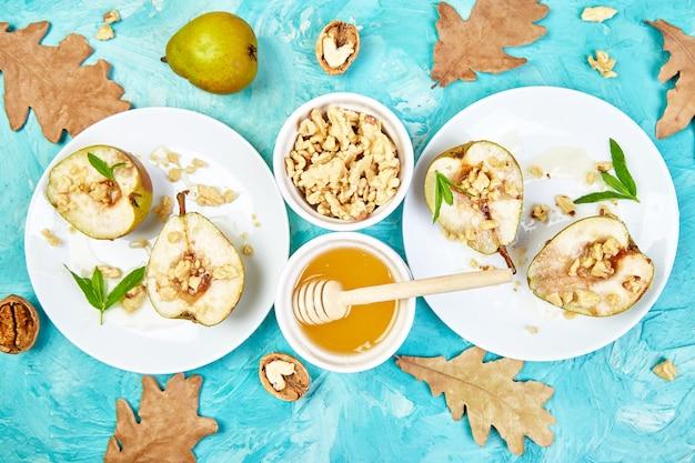 Sabrosas peras asadas con miel y nueces sobre tabla de fondo azul.