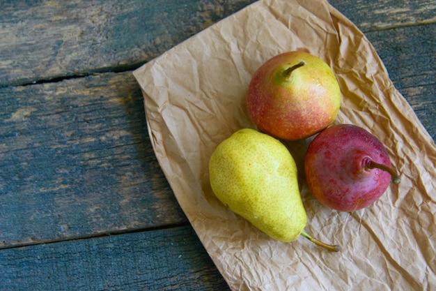 Sabrosas ripy jugosas coloridas peras jugosas en madera