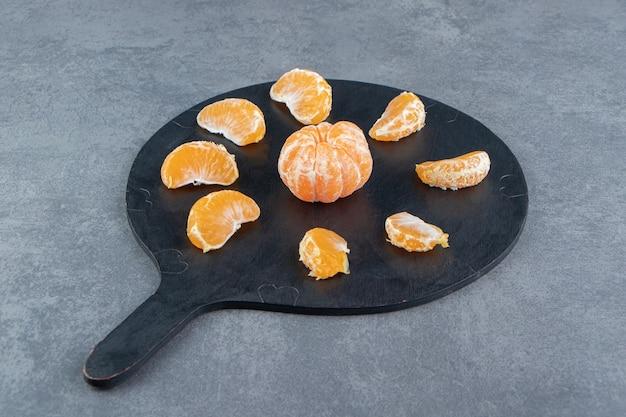 Sabrosas rodajas de mandarina en la tabla de cortar.
