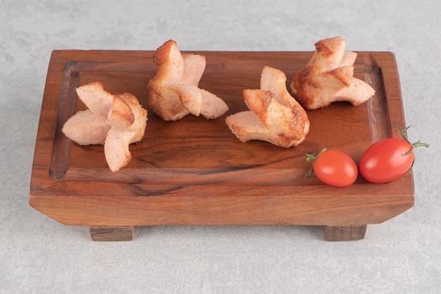 Sabrosas salchichas a la parrilla con tomates sobre tabla de madera.