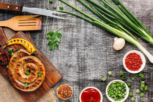 Sabrosas salchichas a la parrilla y verduras frescas sobre fondo viejo