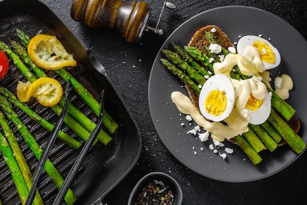 Sabrosas tostadas con espárragos, huevos y salsa.