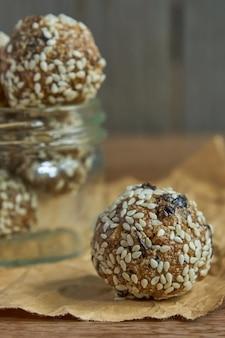 Sabrosas trufas veganas de proteínas crudas o bolas de energía con ciruelas pasas, semillas y nueces en un frasco de madera