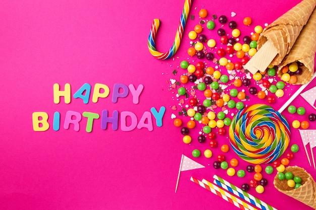 Sabroso apetitoso accesorios para fiestas feliz cumpleaños sobre fondo rosa brillante
